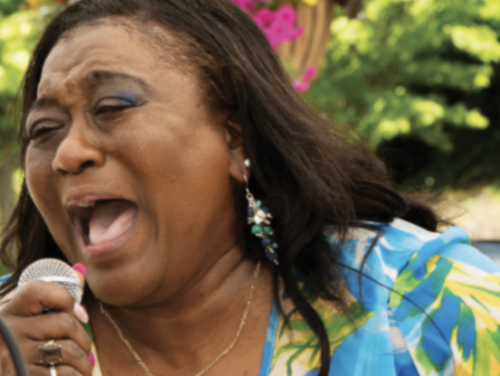 Gospel singer, Mary D. Williams, singing and holding a microphone outside.