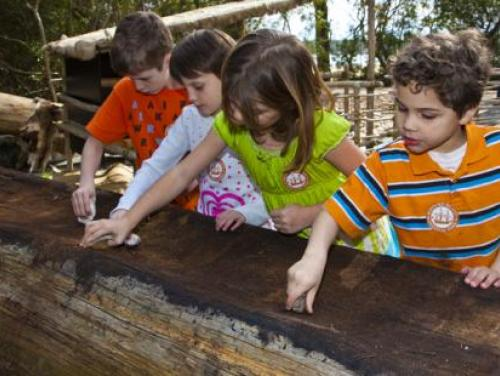Kids scrapping in the inside of the dugout canoe in American Indian Town at Roanoke Island Festival Park