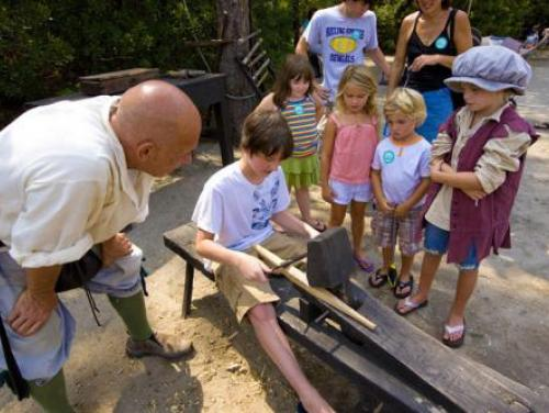 Historic interpreter teaches students how to use the shaving horse in the Settlement Site at Roanoke Island Festival Park