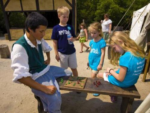 Kids playing Elizabethan games with a historic interpreter in the Settlement Site at Roanoke Island Festival Park