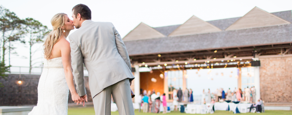 Bride and groom kissing in front of the pavilion at Roanoke Island Festival Park