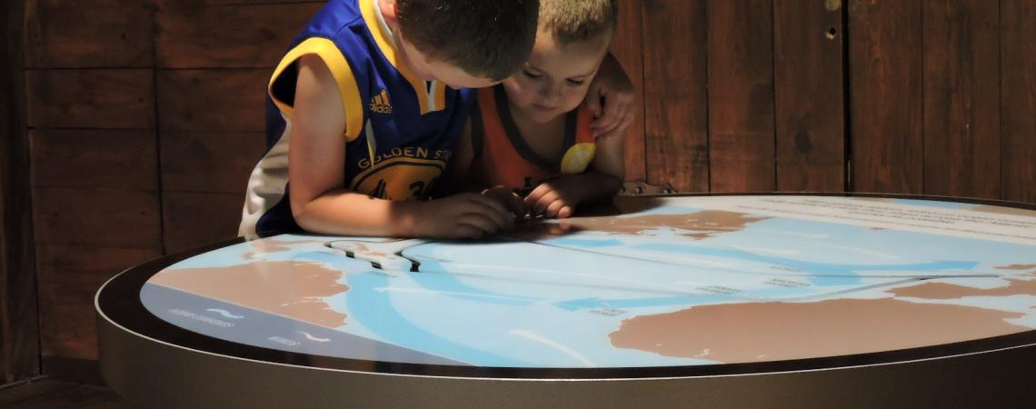 Young boys exploring the new world exhibit at Roanoke Island Festival Park