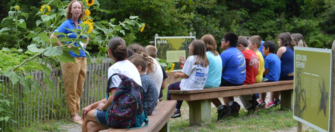 School tour group listening to guide in the American Indian Town garden at Roanoke Island Festival Park