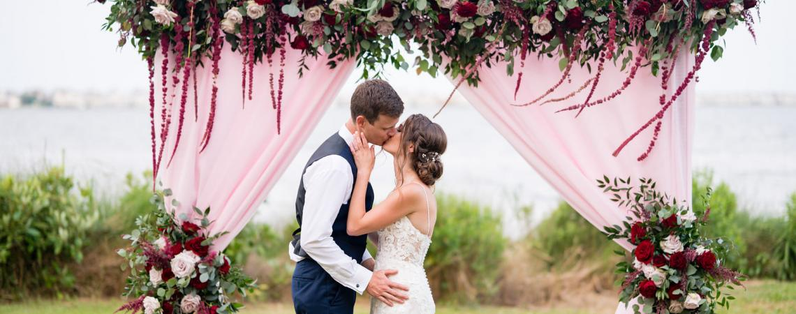 Bride and groom kissing under rose and burgundy floral wedding arch on the waterfront at Roanoke Island Festival Park