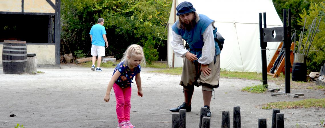 Girl playing nine pin game with settler in the Settlement Site at Roanoke Island Festival Park