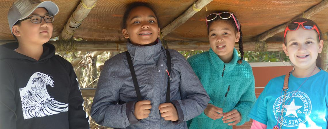 Four middle school students in the watch house exhibit in American Indian Town at Roanoke Island Festival Park