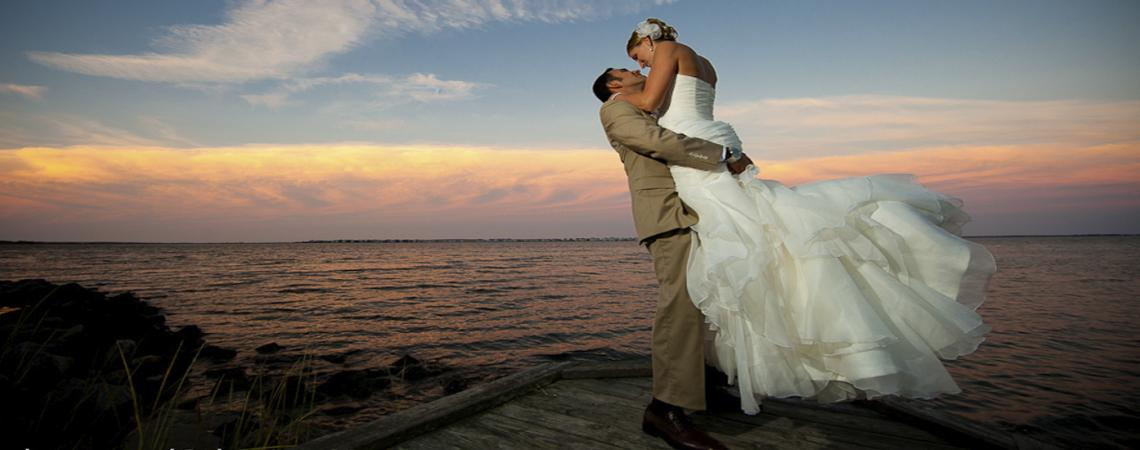 Bride and groom kissing at sunset on the pier at Roanoke Island Festival Park