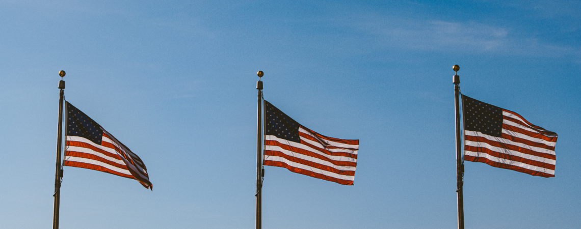 Three American flags waving in the wind against a blue sky.