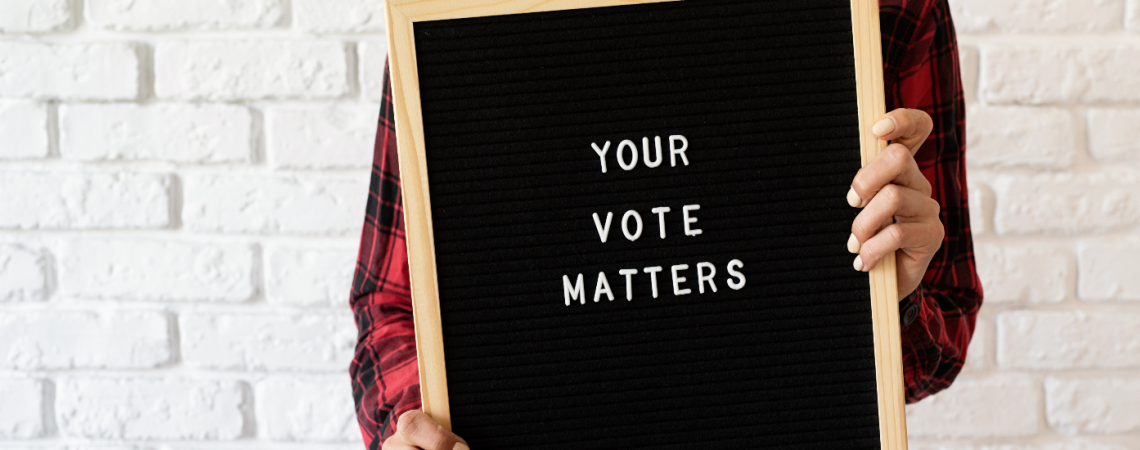 """A person holding a letter board that says """"Your Vote Matters"""""""