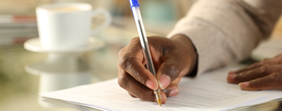 Close-up of a man's hands as he signs a form