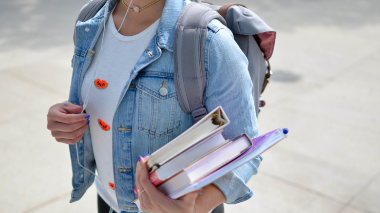 College student with headphones in fashionable clothing, wearing a backpack and carrying textbooks.