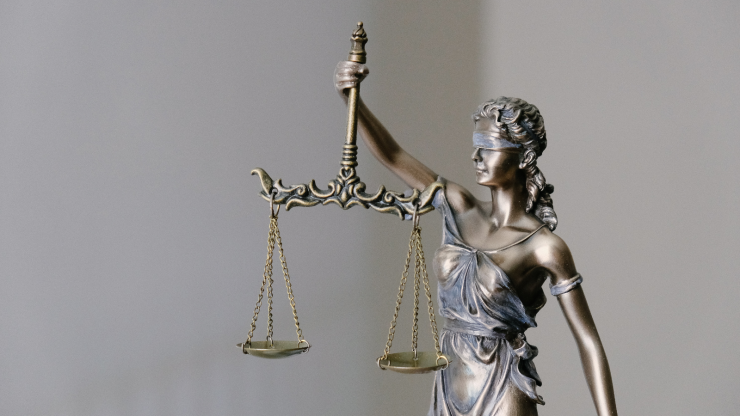 """The courthouse classic """"Lady Justice"""" sculpture of a blindfolded woman holding a sword and set of scales."""