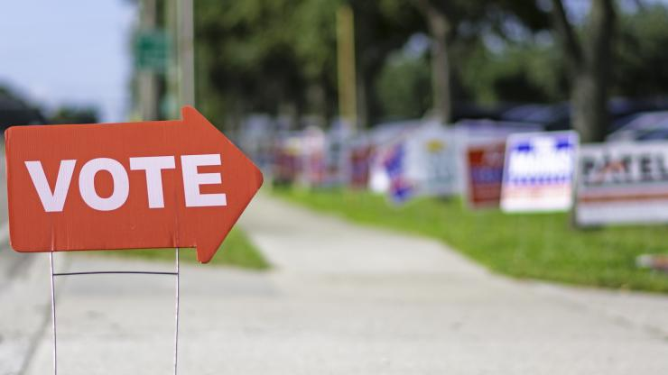 "An arrow-shaped yard sign in front of a polling place that says ""vote."""