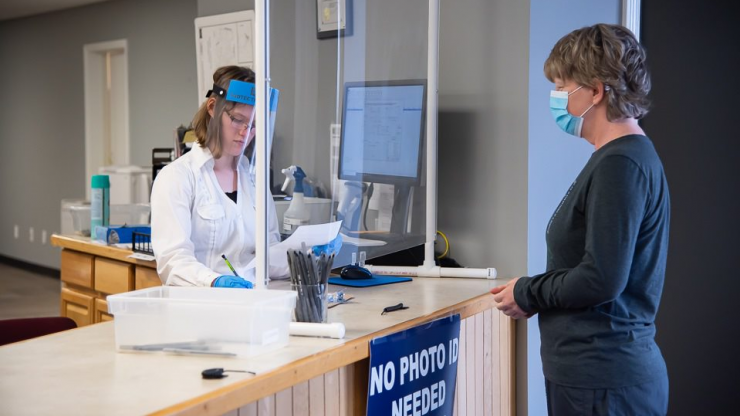 Woman in a mask approaching an election official behind a counter wearing personal protective equipment.