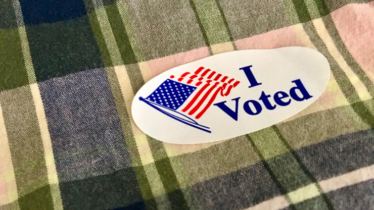 "Close-up of an ""I Voted"" sticker on a plaid shirt."