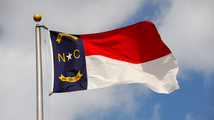 Flag of North Carolina waving against the sky.