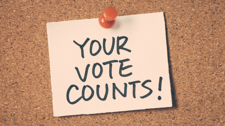 """Your Vote Counts!"" written in permanent marker on a sticky note pinned to a pin board."