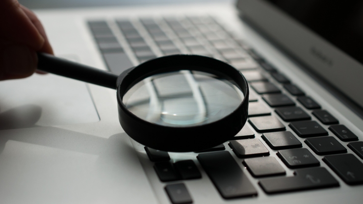 A person hovering a magnifying glass over a laptop keyboard.