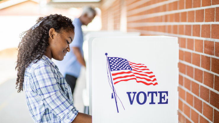 Young person at an outdoor voting booth.