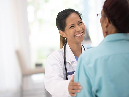 Smiling woman doctor talking with patient
