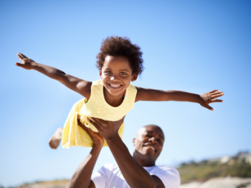 Image of a dad holding his daughter in the air