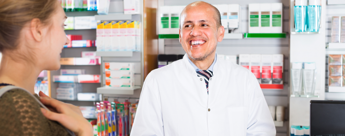 Male pharmacist speaking with a patient