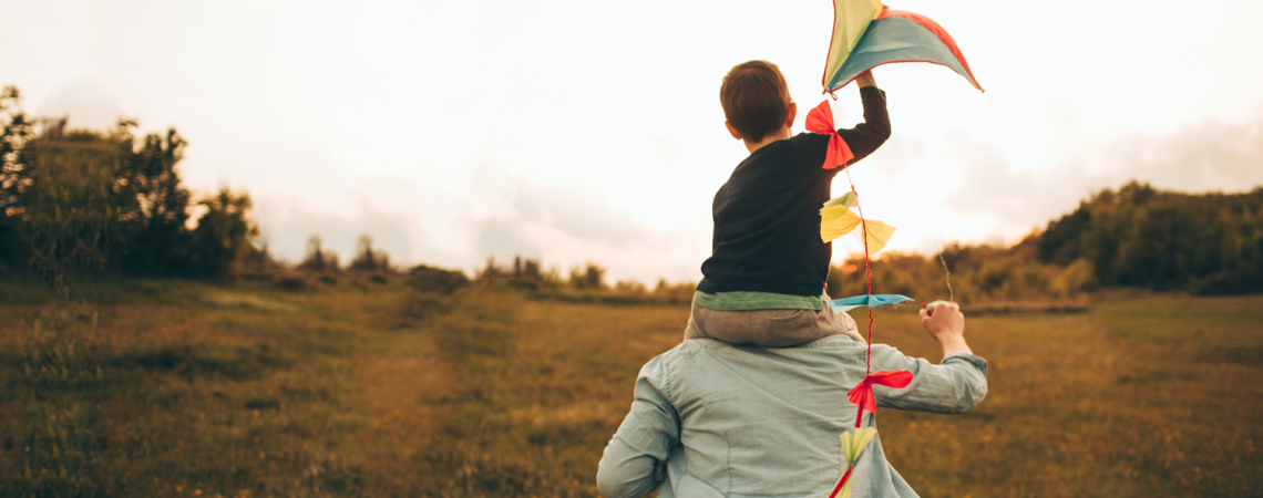 Child on his adults's shoulders flying a kite