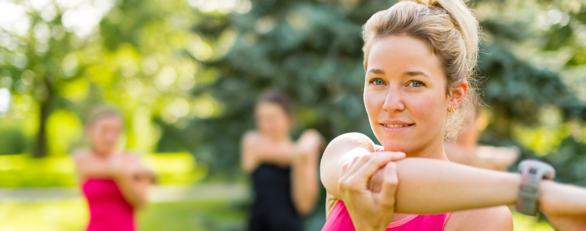 Three women stretching outdoors before working out