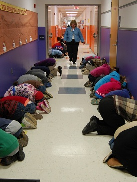students practice a tornado drill in a school hallway