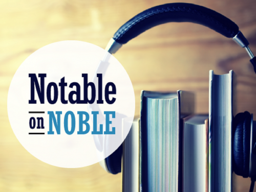 A pair of headphones sit on top of books standing straight up, mimicking ears. The words Notable on NOBLE sit in front