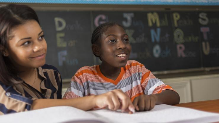 A young student and their teacher sit together listening to a lesson while following along in a braille textbook