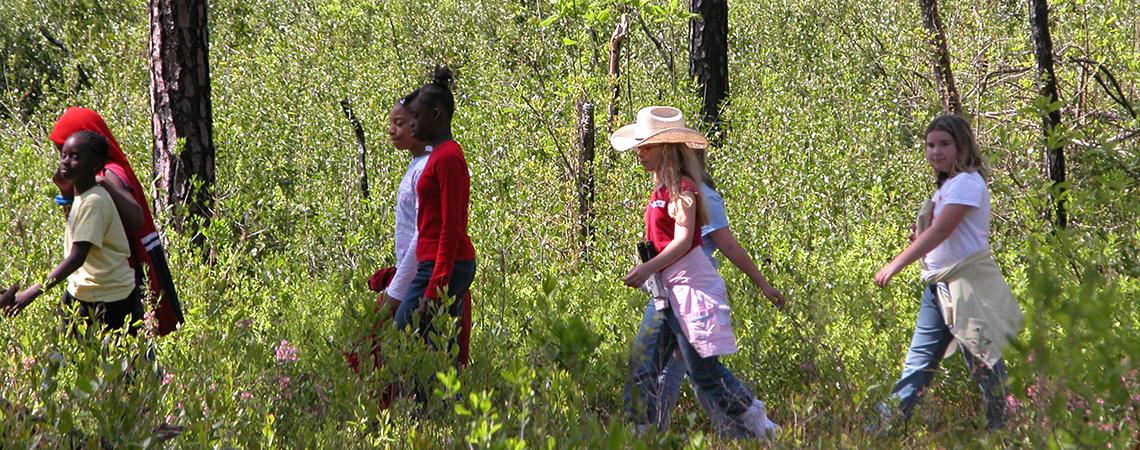 A group of girls enjoy a hike at Jones Lake State Park during a class field trip.