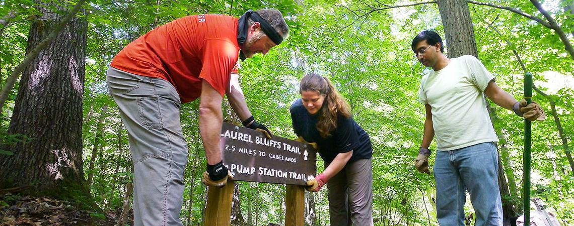 Placing a trail sign at Eno River State Park