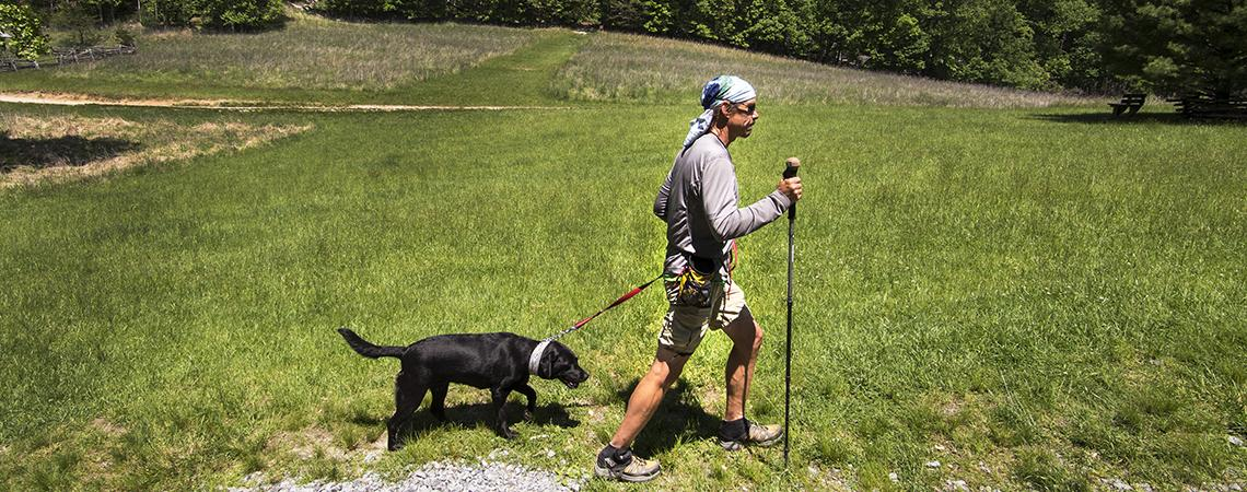 Trevor Thomas hikes with his guide dog at Stone Mountain State Park.